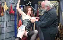Tattooed brunette gets dominated in the dungeon
